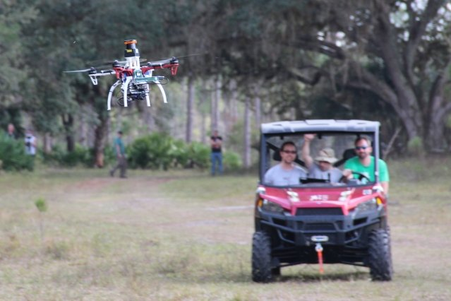 Researchers trail a drone on a test flight outdoors.