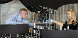 Professor W. E. Moerner, left, and postdoctoral scholar Anna-Karin Gustavsson position a sample on the new TILT3D microscope