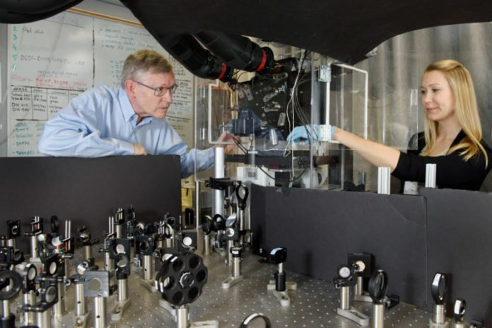 Professor W. E. Moerner, left, and postdoctoral scholar Anna-Karin Gustavsson position a sample on the new TILT3D microscope