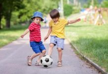Two cute little kids, playing football together, summertime