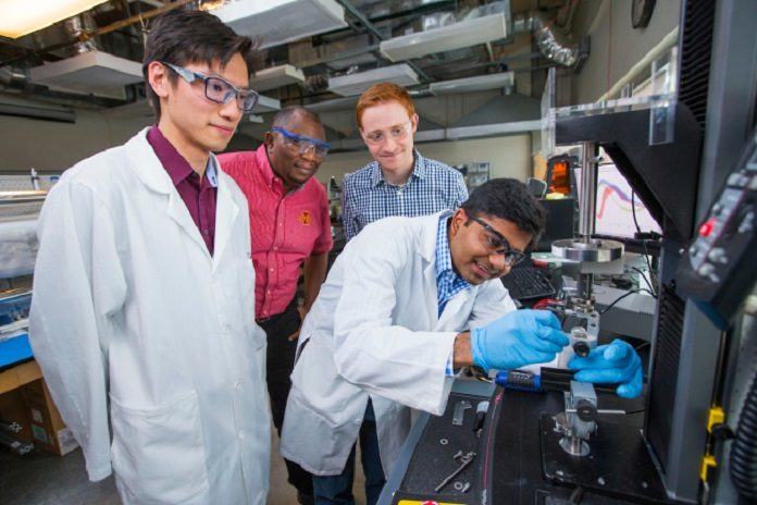 Iowa State engineers -- left to right, Boyce Chang, Martin Thuo, Michael Bartlett and Ravi Tutika -- helped develop and describe a new smart material. Here they examine an instrument used for mechanical testing of material properties. Larger photo
