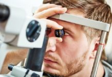 Male patient under eye vision examination in eyesight ophthalmological correction clinic