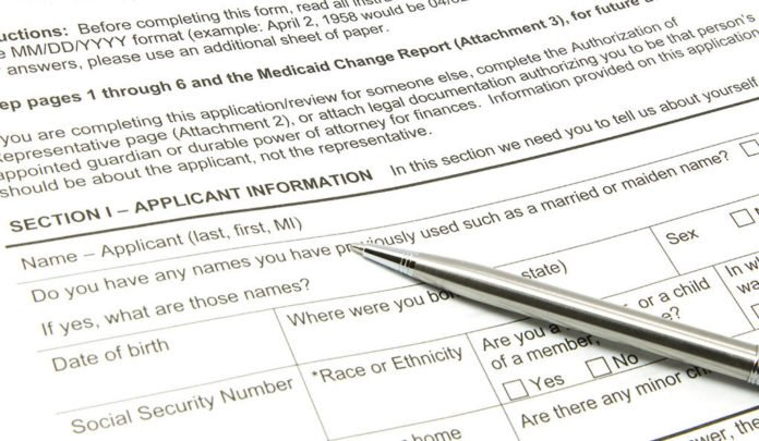 A Medicaid application ready to be filled out with a silver pen.
