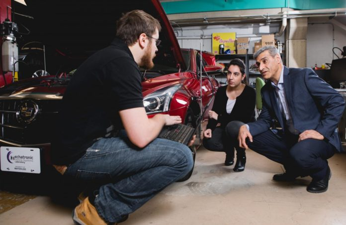This is a photo of new valve technology that promises cheaper, greener engines, Amir Khajepour, a professor of mechanical and mechatronics engineering at Waterloo, in his lab working with his students