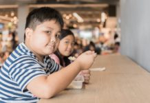 sister eating box lunch in food court, fastfood concept