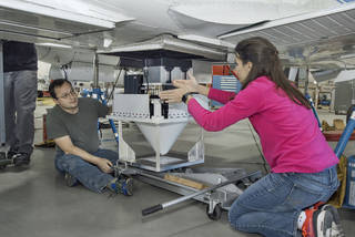 Engineers Raquel Rodriguez Monje and Fabien Nicaise discuss placement of the DopplerScatt radar instrument on the NASA B200 before its final installation onto the aircraft's fuselage. Credits: NASA Photo / Ken Ulbrich