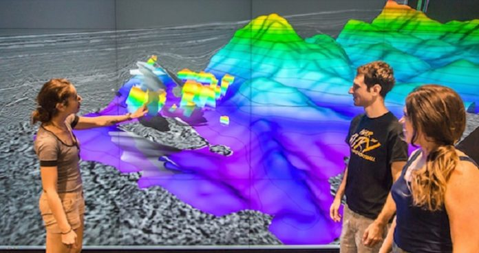 The Galicia group — from left, Rice graduate student Nur Schuba, alumnus Ara Alexanian and graduate research assistant Mari Tesi Sanjurjo — discuss the northwest portion of the 3-D seismic volume at Rice's Visualization Lab. Photo by Gary Linkevich