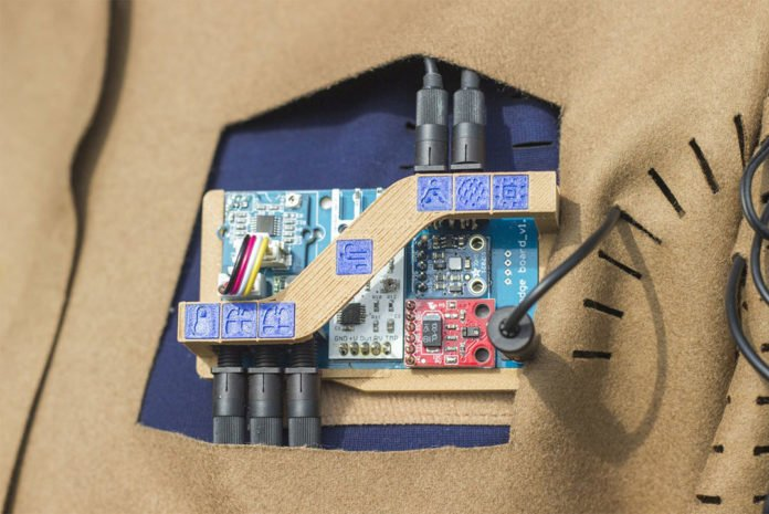 3D prints and laser-cut icons on the meditation suit's fabric indicate where the sensors and cable connections are located.