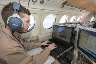 Radar operator Alexander Winteer monitors incoming wind data from the DopplerScatt radar instrument during a science flight off the California Coast on March 5, 2018. Credits: NASA Photo / Carla Thomas