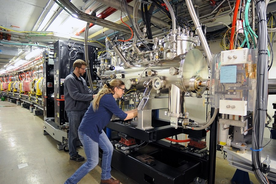Matthew Kasa and Susan Bettenhausen of the APS Accelerator Division Magnetic Devices Group put the finishing touches on installation of the Helical Superconducting Undulator in Sector 7 of the APS storage ring. (Image by Argonne National Laboratory / Richard Fenner.)