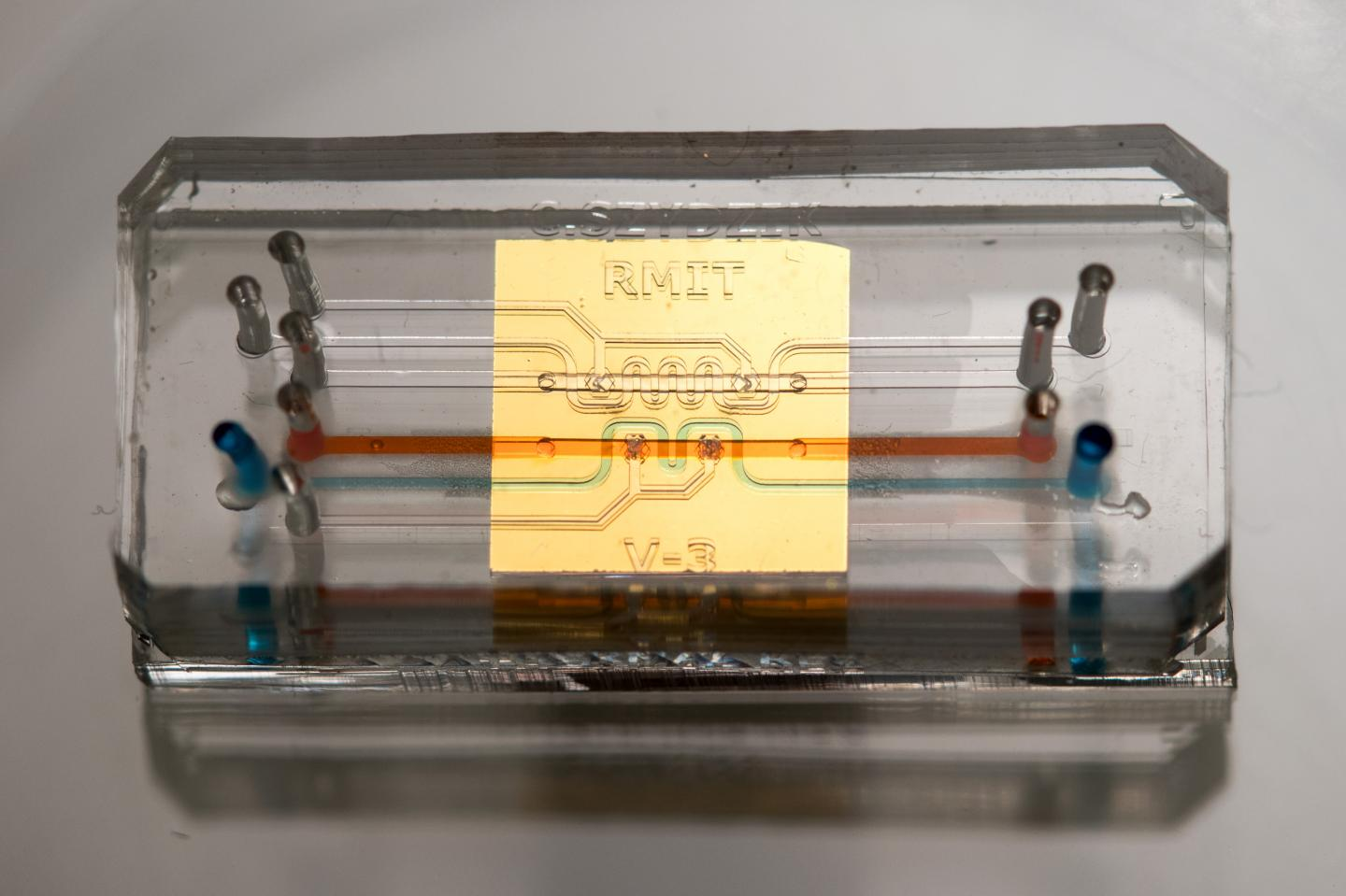 The integrated device showing the microfluidic chip beneath the gold-coloured sensor. Key micro channels - orange (primary) and regulation (blue) - are highlighted with flowing coloured dyes.