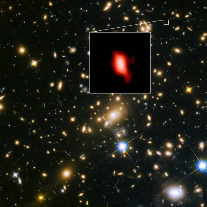This image shows the galaxy cluster MACS J1149.5+2223 taken with the NASA/ESA Hubble Space Telescope; the inset image is the very distant galaxy MACS1149-JD1, seen as it was 13.3 billion years ago and observed with ALMA. Here, the oxygen distribution detected with ALMA is depicted in red. Credit: ALMA (ESO/NAOJ/NRAO), NASA/ESA Hubble Space Telescope, W. Zheng (JHU), M. Postman (STScI), the CLASH Team, Hashimoto et al.