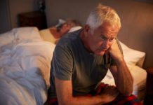 Worried Senior Man In Bed At Night Suffering With Insomnia