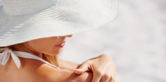 Attractive woman with healthy skin applying sunscreen to shoulder wearing white sun hat