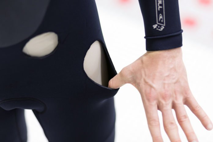 Holes in a wetsuit reveal the thickness of the neoprene material. The new MIT-developed treatment could provide the same amount of insulation with just half the thickness, the researchers say. Photo courtesy of the researchers