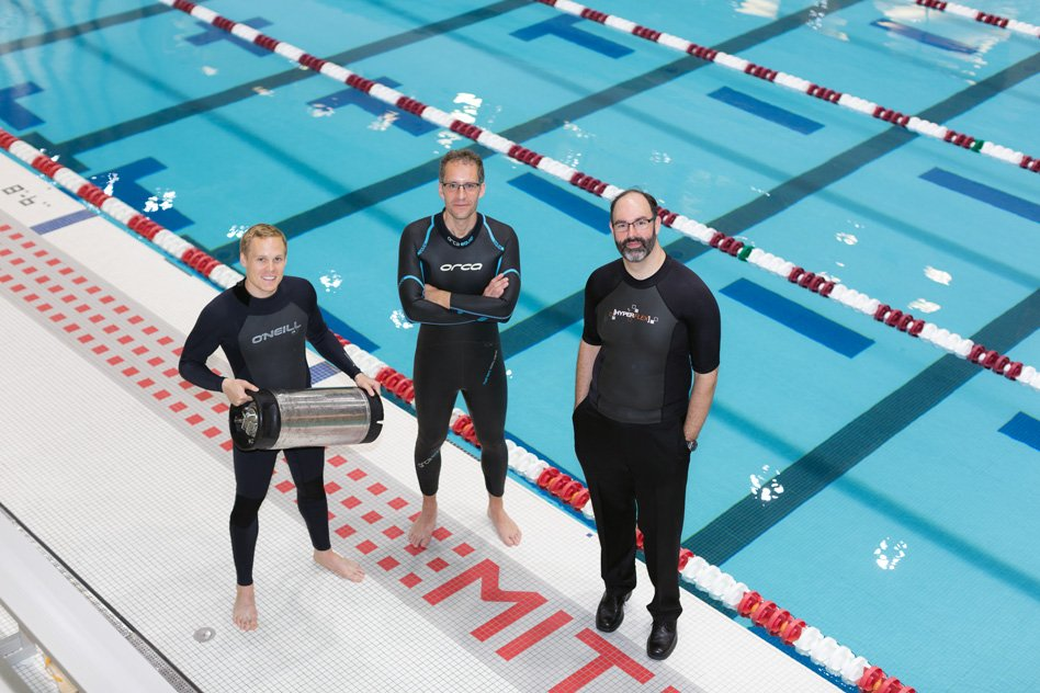 From left, graduate student Anton Cottrill, Professor Jacopo Buongiorno and Professor Michael Strano try out their neoprene wetsuits at a pool at MIT's athletic center. Cottrill is holding the pressure tank used to treat the wetsuits with xenon or krypton.  Photo courtesy of the researchers