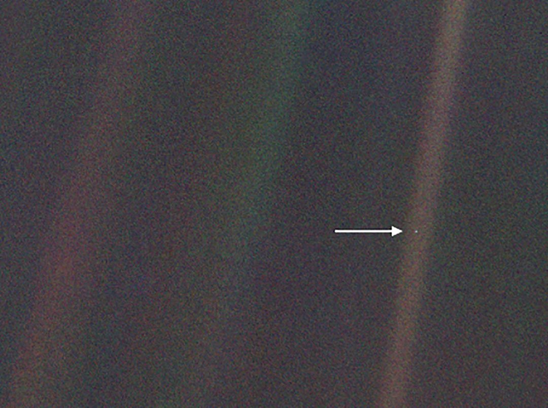 "This image, taken by NASA's Voyager 1 spacecraft from beyond the orbit of Neptune, shows planet Earth as seen from about 3.7 billion miles (5.9 billion km) away. Earth appears as a very small point of light in the right half of the image, indicated by an arrow. Dubbed the ""Pale Blue Dot,"" the image illustrates just how small an Earth-sized planet appears from far away. Credit: NASA/JPL-Caltech"