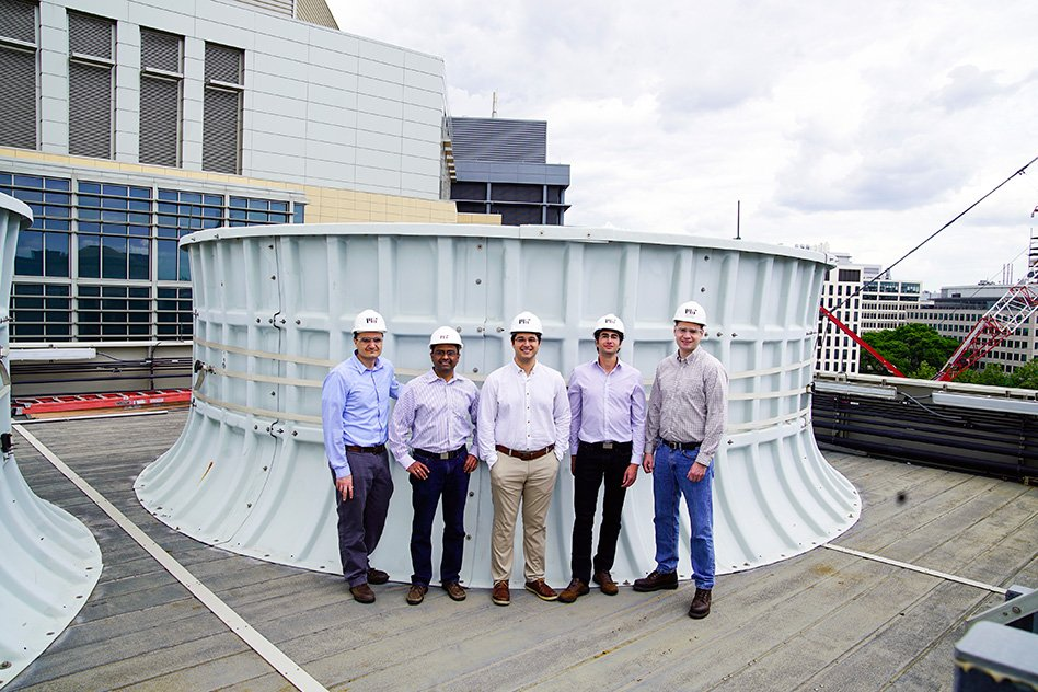 On the roof of the Central Utility Plant building, standing in front of one of the cooling towers, are (left to right): Seth Kinderman, Central Utility Plant engineering manager; Kripa Varanasi, associate professor of mechanical engineering; recent doctoral graduates Karim Khalil and Maher Damak; and Patrick Karalekas, plant engineer, Central Utilities Plant.  Image: Melanie Gonick/MIT