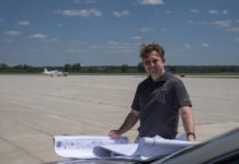 Adam Baxmeyer, Purdue University Airport manager of operations, reviews plans near the airport runway. Purdue is one of the few smaller airports with a traffic control tower. A Purdue-developed technology launched by Bluemac Analytics can help airports improve operations data collection. (Photo by Oren Darling, Purdue Research Foundation)