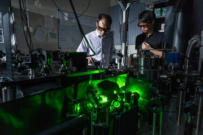 Tongcang Li and Jonghoon Ahn have levitated a nanoparticle in vacuum and driven it to rotate at high speed, which they hope will help them study the properties of vacuum and quantum mechanics. (Purdue University photo/Vincent Walter)