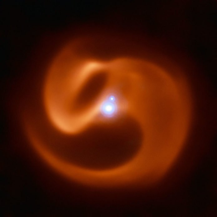 The VISIR instrument on ESO's VLT captured this stunning image of a newly-discovered massive binary star system. Nicknamed Apep after an ancient Egyptian deity, it could be the first gamma-ray burst progenitor to be found in our galaxy. Apep's stellar winds have created the dust cloud surrounding the system, which consists of a binary star with a fainter companion. With 2 Wolf-Rayet stars orbiting each other in the binary, the serpentine swirls surrounding Apep are formed by the collision of two sets of powerful stellar winds, which create the spectacular dust plumes seen in the image. The reddish pinwheel in this image is data from the VISIR instrument on ESO's Very Large Telescope (VLT), and shows the spectacular plumes of dust surrounding Apep. The blue sources at the centre of the image are a triple star system — which consists of a binary star system and a companion single star bound together by gravity. Though only two star-like objects are visible in the image, the lower source is in fact an unresolved binary Wolf-Rayet star. The triple star system was captured by the NACOadaptive optics instrument on the VLT. Credit:ESO/Callingham et al.