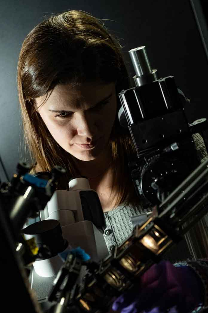 Rice University graduate student Lauren McCarthy adjusts the polarizer she used to discover a fundamentally different form of light-matter interaction in experiments with gold nanoparticles. Photo by Jeff Fitlow