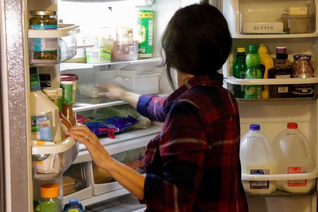 Kristi Mielke puts groceries into her refrigerator. She says her family tries to cut down on food waste by planning their meals and only buying what they need, but that sometimes leftovers get thrown in the trash.