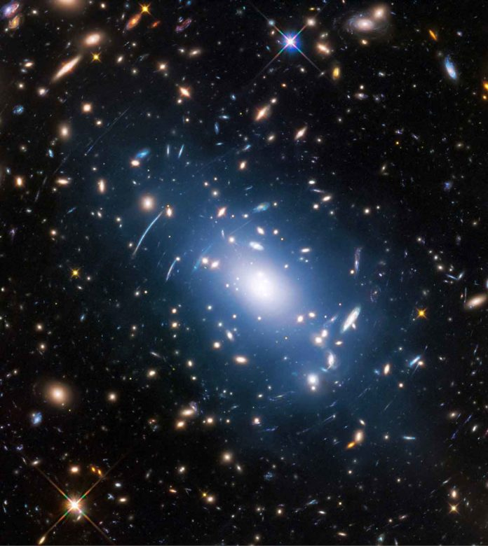 Abell S1063, a galaxy cluster, was observed by the NASA/ESA Hubble Space Telescope as part of the Frontier Fields programme. The huge mass of the cluster — containing both baryonic matter and dark matter — acts as cosmic magnification glass and deforms objects behind it. In the past astronomers used this gravitational lensing effect to calculate the distribution of dark matter in galaxy clusters. A more accurate and faster way, however, is to study the intracluster light (visible in blue), which follows the distribution of dark matter. Credit: NASA, ESA, and M. Montes (University of New South Wales, Sydney, Australia)