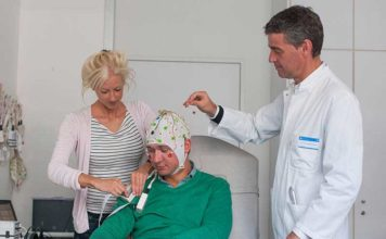 Laura Tiemann, first author of the new study about pain perception, prepares together with Markus Ploner, Heisenberg Professor for Human Pain Research, a volunteer for the EEG-measurements. (Image: K. Bauer / TUM)