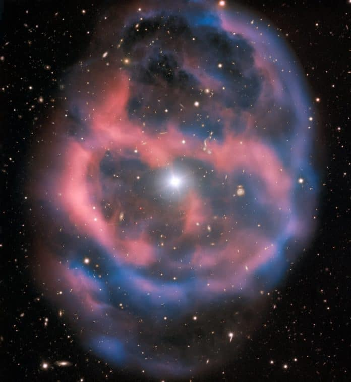 The faint, ephemeral glow emanating from the planetary nebula ESO 577-24 persists for only a short time — around 10,000 years, a blink of an eye in astronomical terms. ESO's Very Large Telescope captured this shell of glowing ionised gas — the last breath of the dying star whose simmering remains are visible at the heart of this image. As the gaseous shell of this planetary nebula expands and grows dimmer, it will slowly disappear from sight. This stunning planetary nebula was imaged by one of the VLT's most versatile instruments, FORS2. The instrument captured the bright, central star, Abell 36, as well as the surrounding planetary nebula. The red and blue portions of this image correspond to optical emission at red and blue wavelengths, respectively. An object much closer to home is also visible in this image — an asteroid wandering across the field of view has left a faint track below and to the left of the central star. And in the far distance behind the nebula a glittering host of background galaxies can be seen.