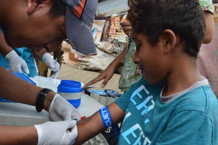 Study personnel collect samples in a neighborhood in Managua in June 2017 from participants in the Nicaraguan Pediatric Dengue Cohort Study (PDCS), a long-standing pediatric dengue cohort established in 2004. Image credit: Sustainable Sciences Institute, Paolo Harris Paz.