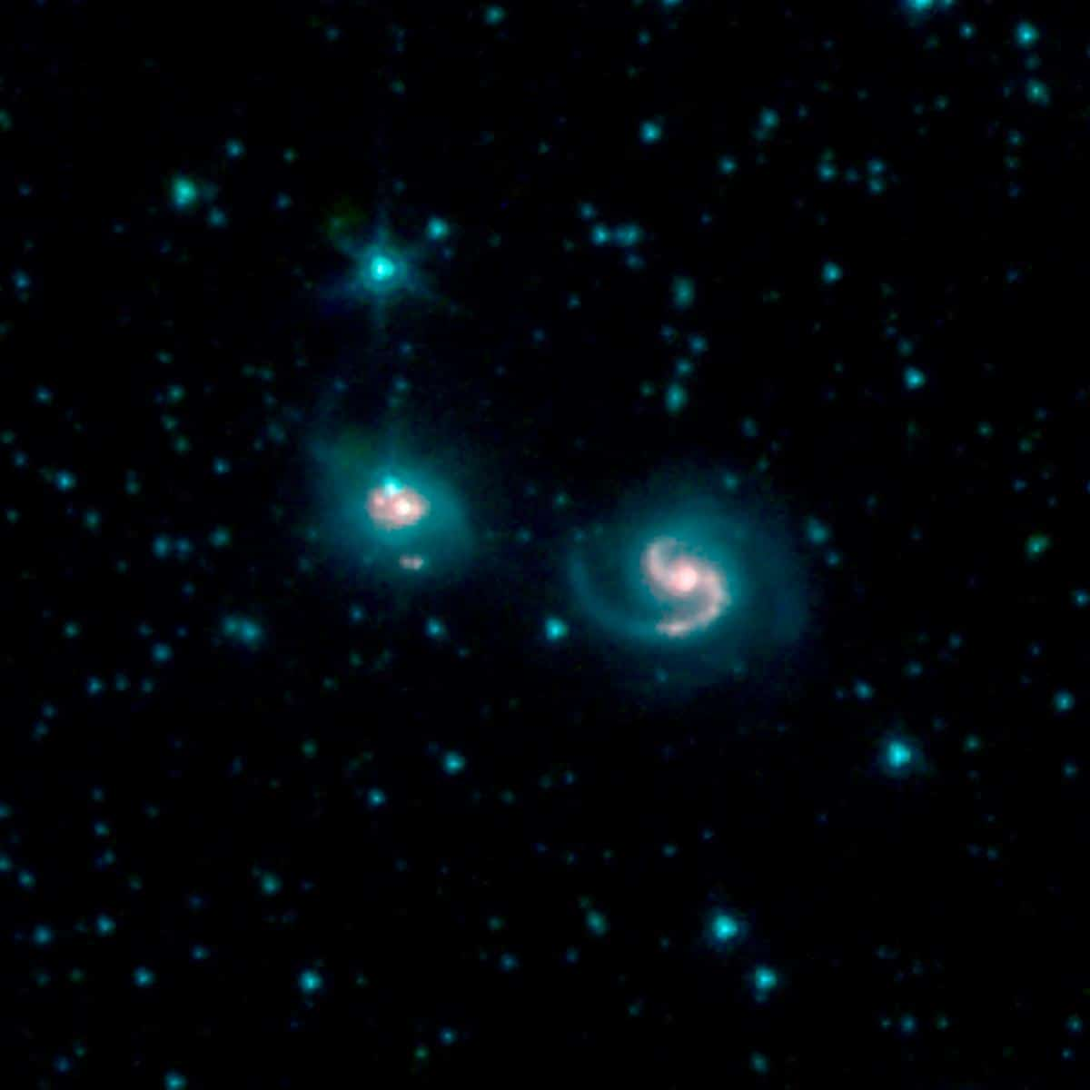 This image shows the merger of two galaxies, known as NGC 6786 (right) and UGC 11415 (left), also collectively called VII Zw 96. It is composed of images from three Spitzer Infrared Array Camera (IRAC) channels: IRAC channel 1 in blue, IRAC channel 2 in green and IRAC channel 3 in red. Credit: NASA/JPL-Caltech