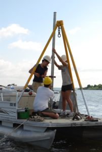 Taking a soil core from underwater soil is a bit trickier than soil that's on the surface. Scientists have to utilize boats and plunge the sampling equipment through water and down into the soil.  CREDIT Mark Stolt