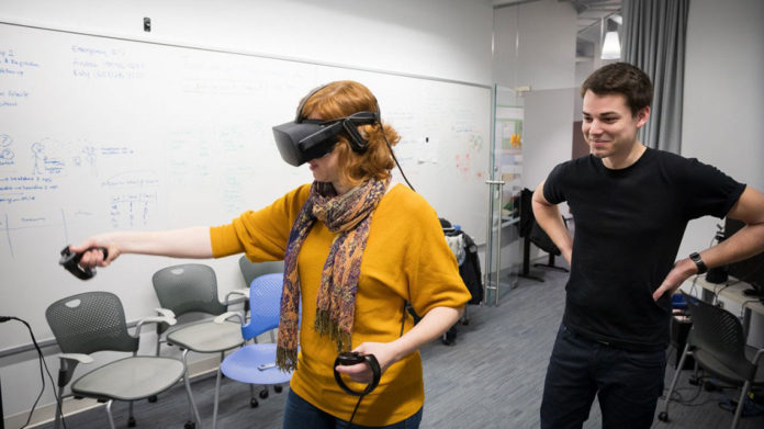 Jack Madden, doctoral candidate in the field of astronomy, watches as Andrea Stevenson Won, assistant professor of communication and director of the Virtual Embodiment Lab, uses a virtual reality simulator.