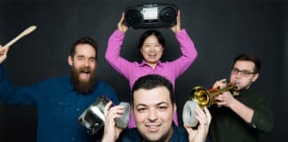 Boston University mechanical engineers have created synthetic, sound-silencing structures—acoustic metamaterials—that can block 94% of sounds. Reza Ghaffarivardavagh (ENG) (front center) holds two of the open, ringlike structures over his ears while Stephan Anderson (MED) (left), Xin Zhang (ENG) (rear center), and Jacob Nikolajczyk (ENG) (right) make a racket. Photo by Cydney Scott