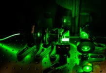 The experimental setup used by the researchers to test their magnetic sensor system, illuminated by green laser light.