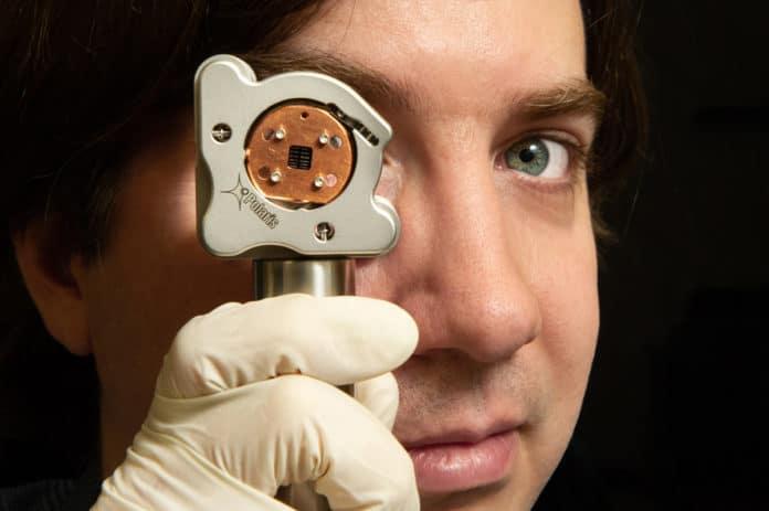 Thomas Corbitt looks through the custom-built device used to measure quantum radiation pressure noise. Credit: Elsa Hahne/LSU