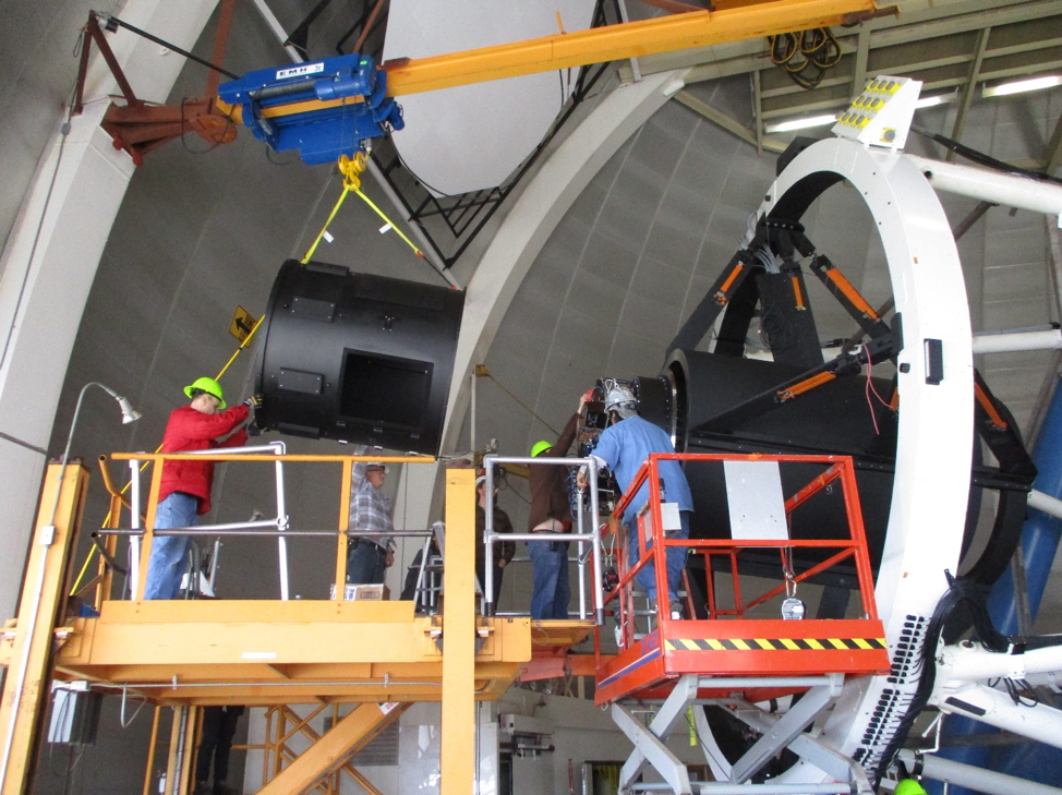 Workers raise DESI's commissioning instrument into position for installation. The instrument is designed to test the performance of DESI's lenses. (Credit: NOAO/AURA/NSF)