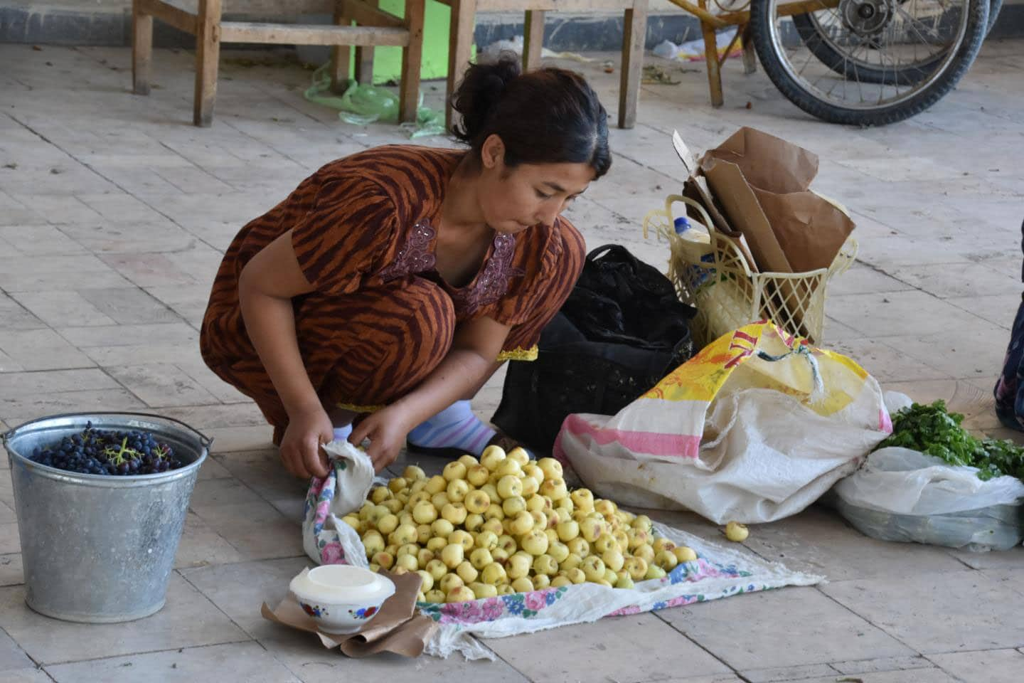 Venders in every Central Asian bazaar sell a diverse array of apples. This women in the Bukhara bazaar is selling a variety of small sweet yellow apples, which she locally cultivated in Uzbekistan. Some of the fruits sold in these markets today travel great distances, similar to how they would have during the peak of the Silk Road.  CREDIT Robert Spengler