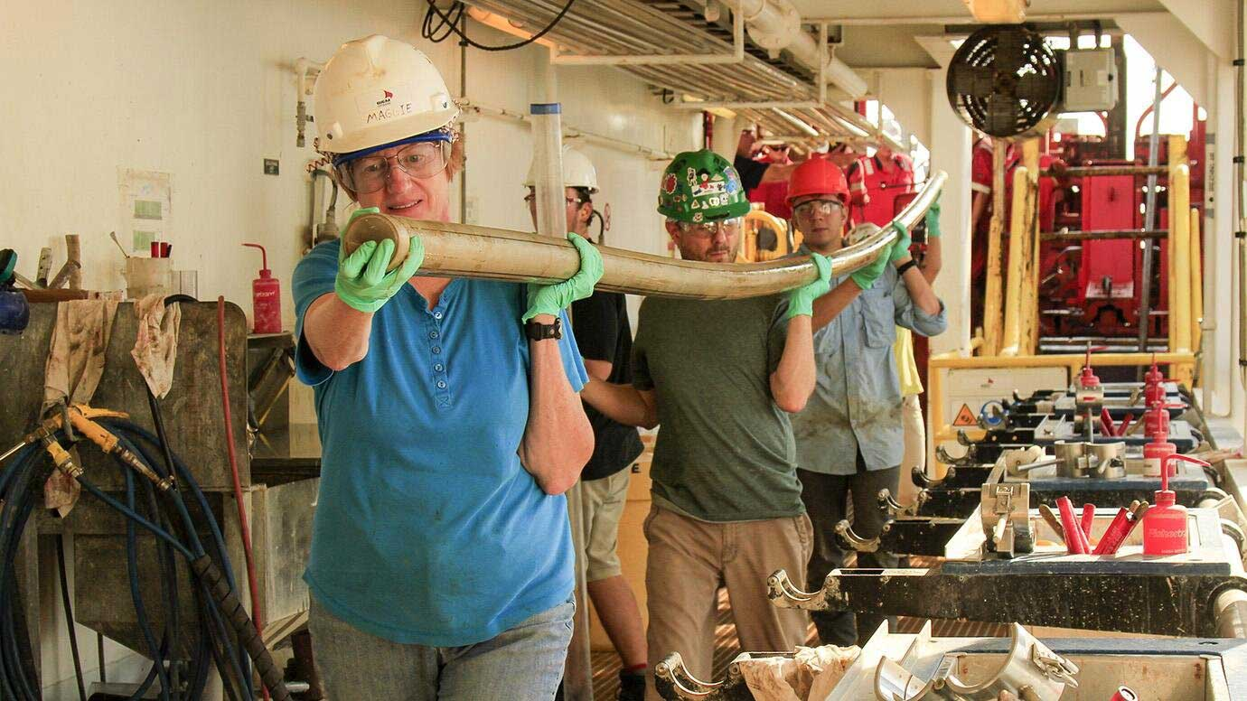 Scientists carry a core of rock extracted by drill. Credit: Clara Blättler