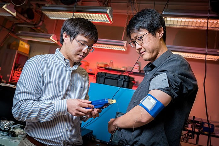 Renkun Chen (left), UC San Diego professor of mechanical and aerospace engineering, measures the temperature of the prototype cooling/heating system worn by Sahngki Hong (right), the study's first author.