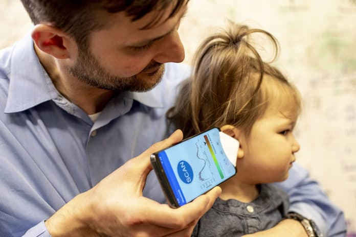 Dr. Randall Bly, an assistant professor of otolaryngology at the UW School of Medicine who practices at Seattle Children's Hospital, uses the app to check his daughter's ear.Dennis Wise/University of Washington