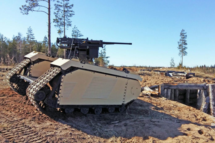 While its human controllers crouch in the relative safety of the trenches, the THeMIS robot rolls over terrain and fires when directed at targets on another hill. (Milrem Robotics)