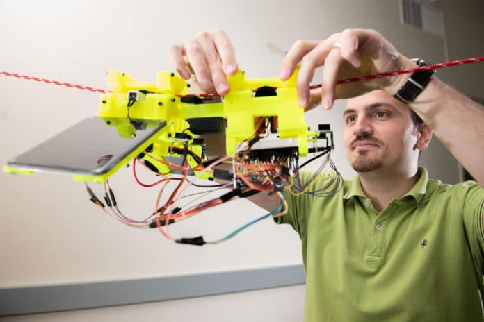 Graduate Research Assistant Gennaro Notomista shows the components of SlothBot on a cable in a Georgia Tech lab./ Image: Georgia Tech