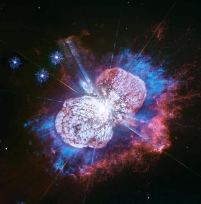 Telescopes, including Hubble, have monitored the Eta Carinae star system for more than two decades. It has been prone to violent outbursts, including an episode in the 1840s during which ejected material formed the bipolar bubbles seen here. Now, using Hubble's Wide Field Camera 3 to probe the nebula in ultraviolet light, astronomers have uncovered the glow of magnesium embedded in warm gas (shown in blue) in places they had not seen it before. The luminous magnesium resides in the space between the dusty bipolar bubbles and the outer shock-heated nitrogen-rich filaments (shown in red). The streaks visible in the blue region outside the lower-left lobe are a striking feature of the image. These streaks are created when the star's light rays poke through the dust clumps scattered along the bubble's surface. Wherever the ultraviolet light strikes the dense dust, it leaves a long, thin shadow that extends beyond the lobe into the surrounding gas. Eta Carinae resides 7500 light-years away. Credit: NASA, ESA, N. Smith (University of Arizona, Tucson), and J. Morse (BoldlyGo Institute, New York)
