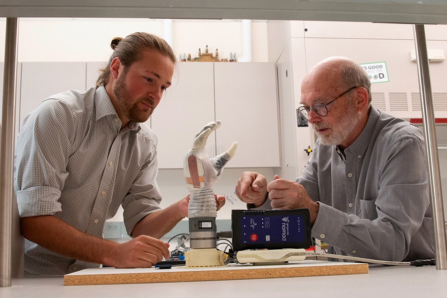 Greg Clark (right) and Jake George (left) with the LUKE arm./ Image Credit: University of Utah College of Engineering.