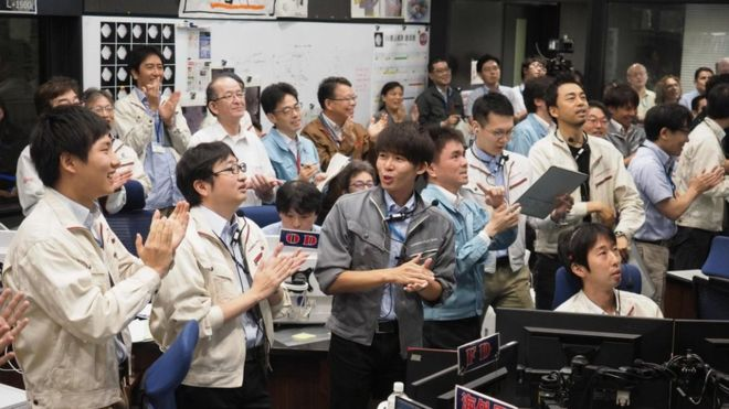 Staff and researchers from Japan's space agency, JAXA, celebrate in the mission control room. AFP / ISAS-JAXA
