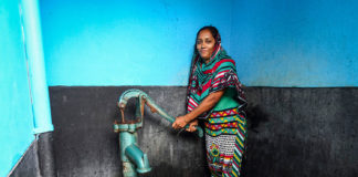 A woman pumps water from a shared community tap in Dhaka, Bangladesh. (Image credit: GMB Akash)