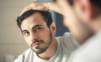 Man observing hair in mirror