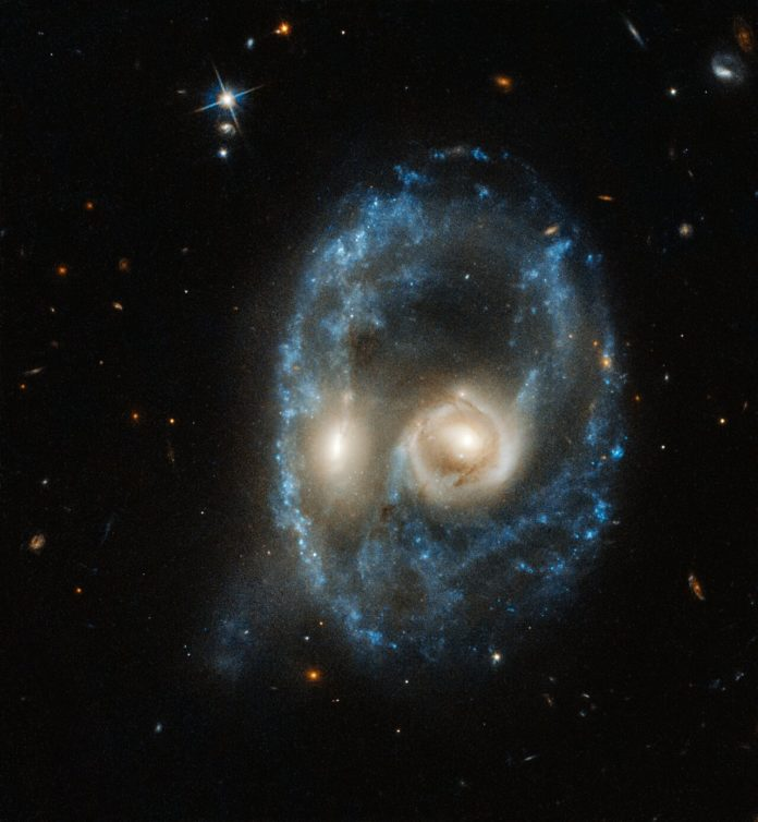 "This new image from the NASA/ESA Hubble Space Telescope captures two galaxies of equal size in a collision that appears to resemble a ghostly face. This observation was made on 19 June 2019 in visible light by the telescope's Advanced Camera for Surveys. Residing 704 million light-years from Earth, this system is catalogued as Arp-Madore 2026-424 (AM 2026-424) in the Arp-Madore ""Catalogue of Southern Peculiar Galaxies and Associations"". Credit: NASA, ESA, J. Dalcanton, B.F. Williams, and M. Durbin (University of Washington)"